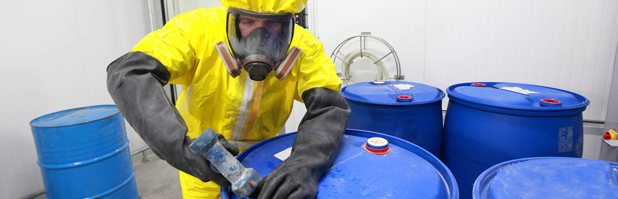 Man with safety suit and mask sealing a barrel of chemicals - Business Protection Specialists