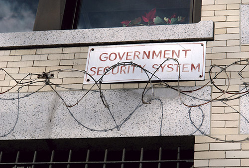 Brick building with government sign and barbed wire surrounding it - Business Protection Specialists