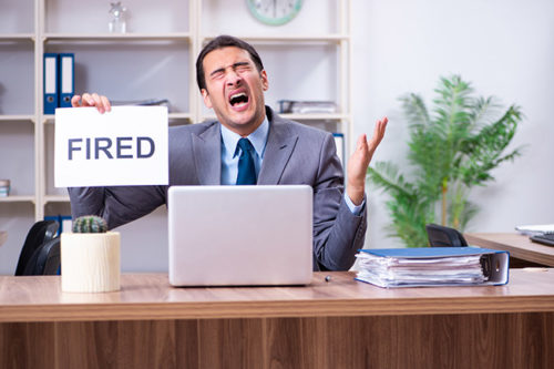 Upset man holding a sign that says fired - Business Protection Specialists